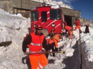 Zug fährt am Oberalppass in Schneerutsch
