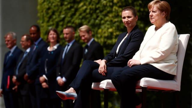 Merkel weicht vom Protokoll ab und sitzt